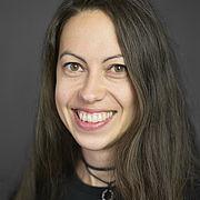 Eine junge Frau mit langen durnkelblonden Haaren und dunkelm Oberteil lächelt freundlich und aufgeschlossen.