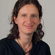 Anne Jaschke hat gelocktes dunkelbraunes Haar. Sie trägt ein dunkles, vorne geschnürtes Oberteil und lächelt freundlich.