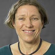 Portrait: Eine Frau mit halblangen Haaren lächelt zuversichtlich. Sie trägt eine dunkele Perlenkette und ein blaues Oberteil.