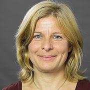 Das freundliche Gesicht einer Frau schaut zwischen blonden halblangen Haaren hervor.