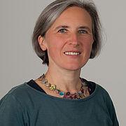 Bärbel Jebens ist eine Frau mittleren Alters, deren freundliches Gesicht von silbergrau durchzogenen Haaren umrahmt wird und eine bunte Kette schmückt den Hals über einem blaugrauen Oberteil.
